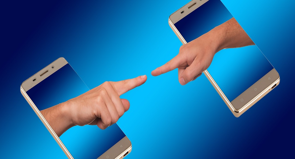Finger pointing to each other from two phone screens